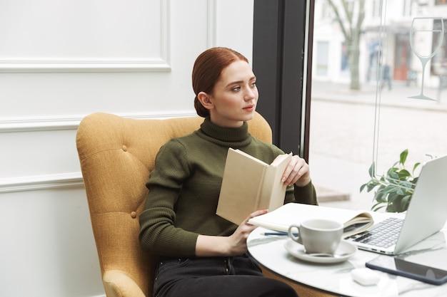 Piękna młoda ruda kobieta relaksuje przy stoliku kawiarnianym w pomieszczeniu, pijąc kawę, czytając książkę