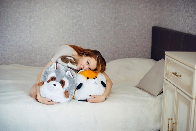 Piękna młoda rudowłosa dziewczyna przytula duże miękkie zabawki, siedząc w łóżku w domu. urocza atrakcyjna kobieta przytula swoje dziecięce zabawki.