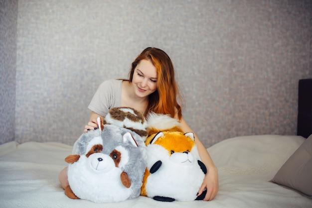 Piękna młoda rudowłosa dziewczyna przytulanie duże miękkie zabawki, siedząc w łóżku w domu. urocza atrakcyjna kobieta przytula swoje dziecięce zabawki.