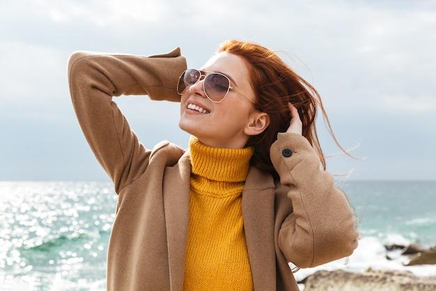 Piękna młoda rudowłosa kobieta nosi płaszcz spaceru na plaży