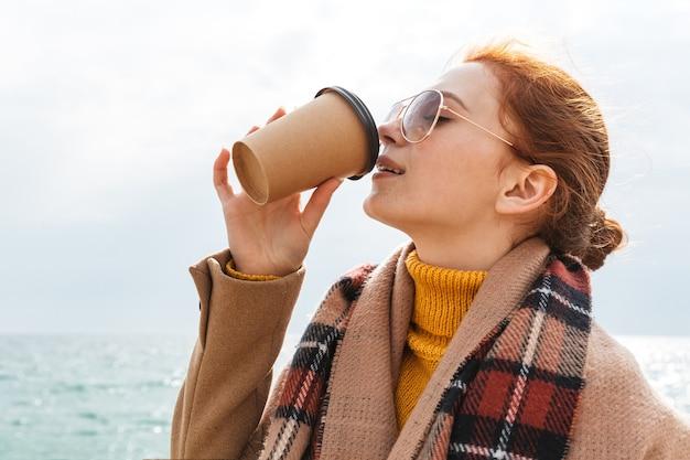 Piękna młoda rudowłosa kobieta w płaszczu spacerująca po plaży, pijąca kawę na wynos