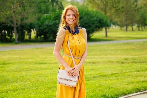 Piękna młoda rudowłosa szkocka kobieta w żółtej sukience ze stylową torbą w letnim parku