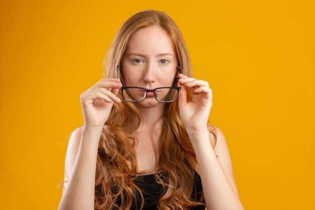 Piękna młoda rudzielec kobieta z kędzierzawym włosy szczęśliwym z jej szkłami. koncepcja pielęgnacji oczu. na żółtej ścianie