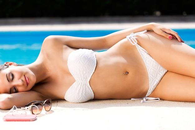 Piękna, młoda, seksowna dziewczyna cieszy się latem przy basenie.