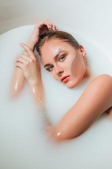 Piękna młoda seksowna dziewczyna o mokrych blond włosach, egzotyczny makijaż, kąpieli z mleczną opalenizną, idealną skórą, salon kosmetyczny i spa dla kobiety.