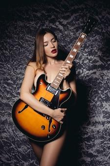 Piękna młoda seksowna kobieta z gitarą. muzyczna dziewczyna