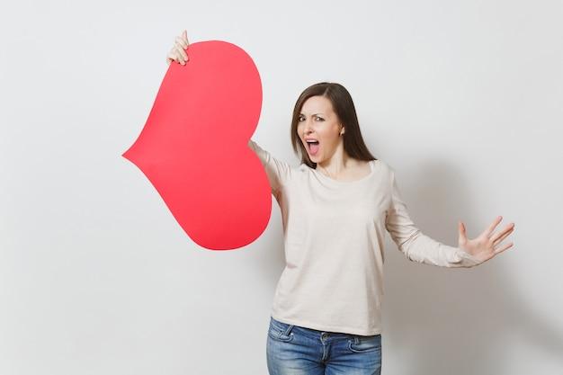Piękna młoda sfrustrowana kobieta trzyma wielkie czerwone serce w rękach na białym tle. skopiuj miejsce na reklamę. miejsce na tekst. koncepcja dzień świętego walentego lub międzynarodowy dzień kobiet.