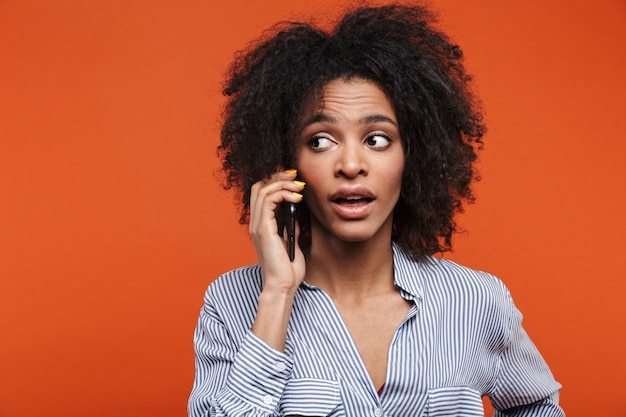 Piękna młoda skoncentrowana afrykańska kobieta wyizolowana na pomarańczowej ścianie rozmawia przez telefon komórkowy.