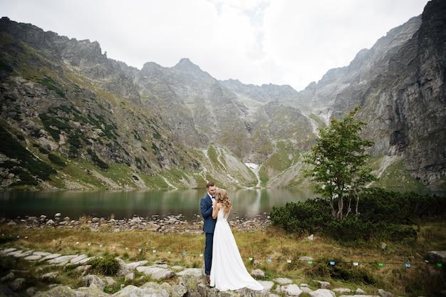 Piękna młoda ślub para fornala i panny młodej pozycja na zielonym skłonie, wzgórze. zachód słońca w karpatach