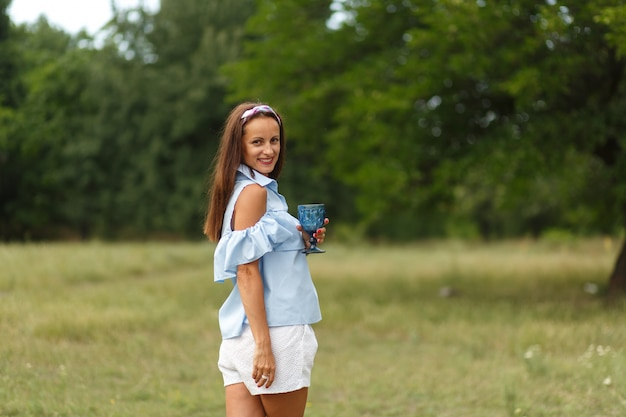 Piękna młoda smilling kobieta wewnątrz przy lampką szampana przy zielonym lato parkiem