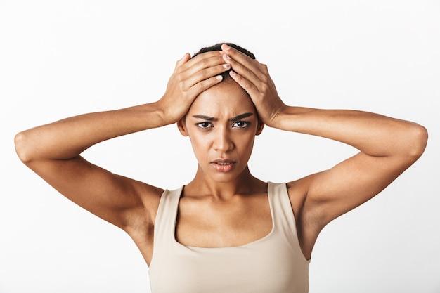 Piękna młoda smutna afrykańska kobieta ubrana niedbale stojąc na białym tle, mając ból głowy