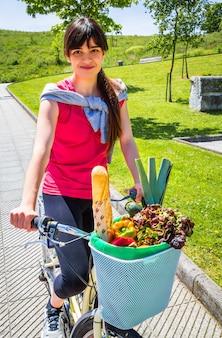 Piękna młoda sportive kobieta z zakupami w koszyku rowerowym w słoneczny letni dzień