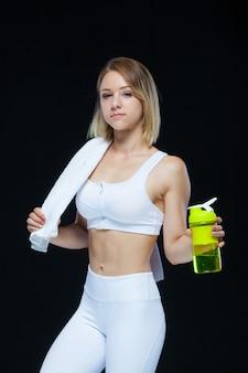 Piękna młoda sportsmenka trzyma butelkę woda i żółty dumbbell