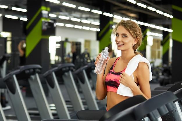 Piękna młoda sporty kobieta odpoczywa po ciężkiego treningu w gym.