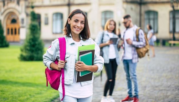 Piękna młoda studencka dziewczyna z plecakiem i książkami przez uniwersytet