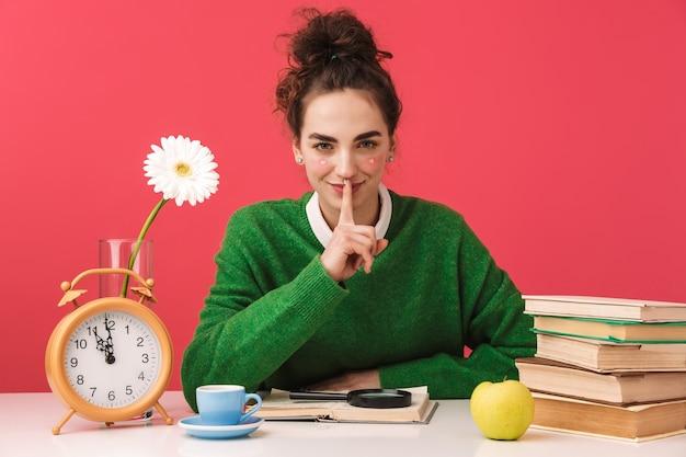 Piękna młoda studentka frajerem dziewczyna siedzi przy stole na białym tle, studiuje z książkami, cisza gest
