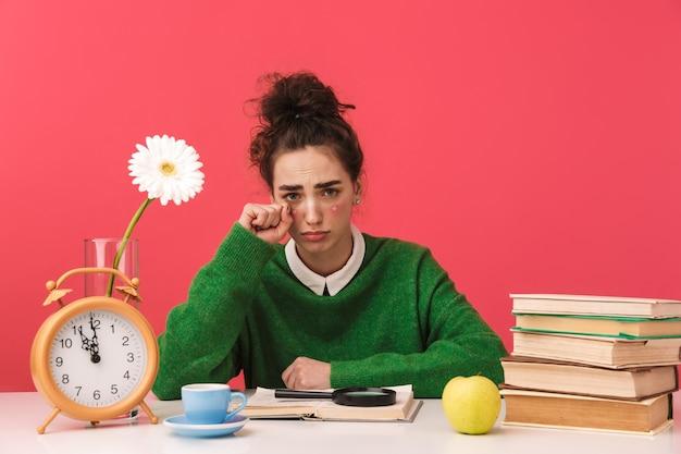 Piękna młoda studentka frajerem dziewczyna siedzi przy stole na białym tle, studiuje z książkami, płacze