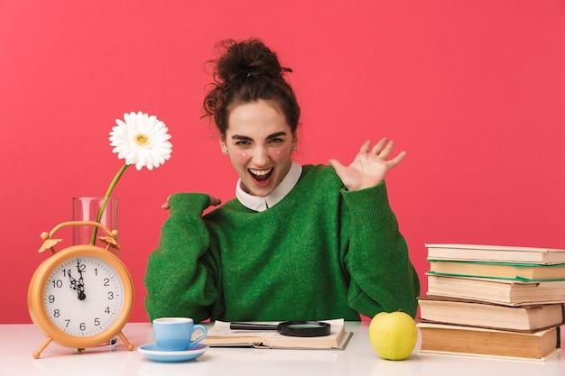 Piękna młoda studentka frajerem dziewczyna siedzi przy stole na białym tle, studiuje z książkami, świętuje sukces