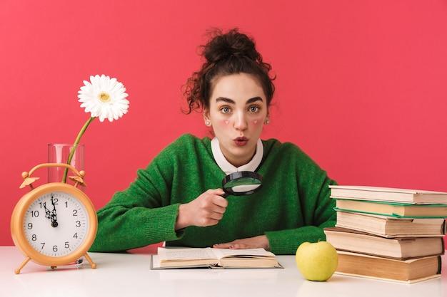 Piękna młoda studentka frajerem dziewczyna siedzi przy stole na białym tle, studiuje z książkami, szkło powiększające