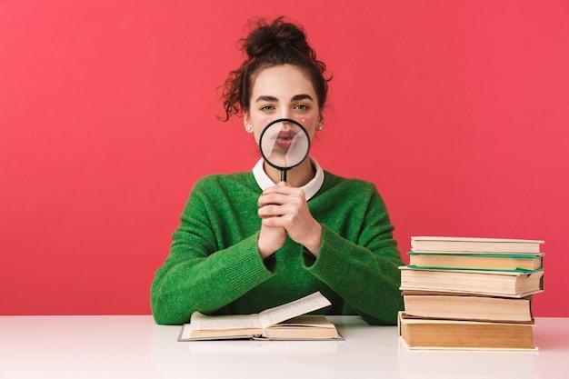 Piękna młoda studentka frajerem dziewczyna siedzi przy stole na białym tle, studiuje z książkami, trzymając szkło powiększające