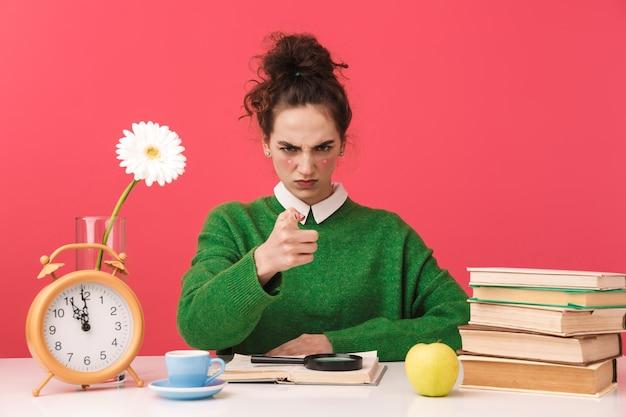 Piękna młoda studentka frajerem dziewczyna siedzi przy stole na białym tle, studiuje z książkami, wskazując palcem