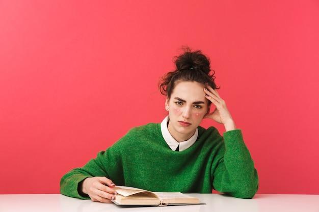 Piękna młoda studentka nerd siedzi przy stole na białym tle, studiuje z książkami