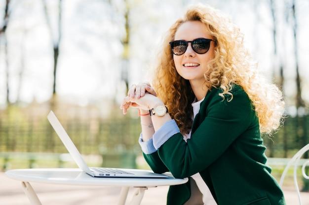 Piękna młoda studentka z pięknymi kręconymi blond włosami elegancko ubrana za pomocą zwykłego laptopa.