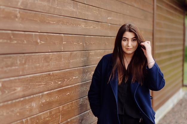 Piękna młoda stylowa dziewczyna w ścianie drewna