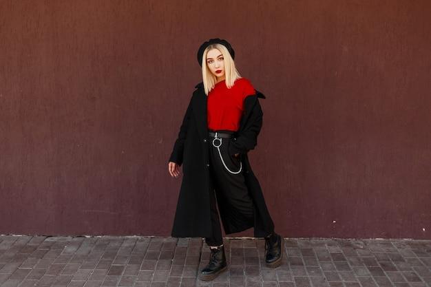 Piękna młoda stylowa kobieta w modnym czarnym płaszczu z czerwoną koszulą i czarnymi skórzanymi butami stojąc i pozując