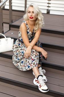 Piękna młoda stylowa kobieta z czerwonymi ustami w sukienka vintage moda z białą torbą i trampki siedzi na schodach na plaży