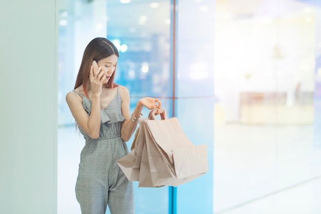 Piękna młoda szczęśliwa azjatycka kobieta z kolorowym torba na zakupy używać smartphone podczas gdy robiący zakupy w centrum handlowym