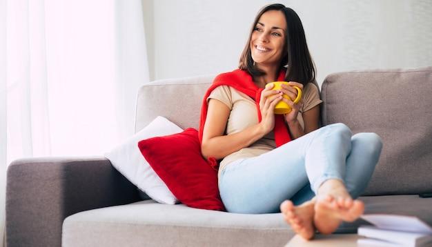 Piękna młoda szczęśliwa brunetka kobieta relaksuje na kanapie w domu i marzy