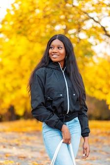 Piękna młoda szczęśliwa czarna kanadyjska kobieta z uśmiechem w swobodnej kurtce z dżinsami spaceruje po parku z żółtymi jesiennymi liśćmi na jesienne wakacje
