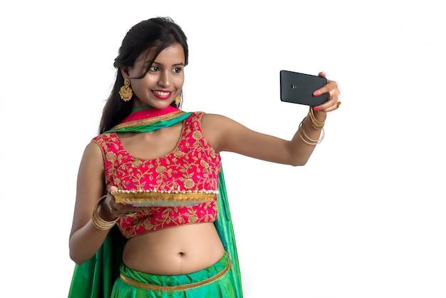 Piękna młoda szczęśliwa dziewczyna bierze selfie z glinianą lampą lub diya podczas festiwalu lekki diwali używać smartphone na białym tle