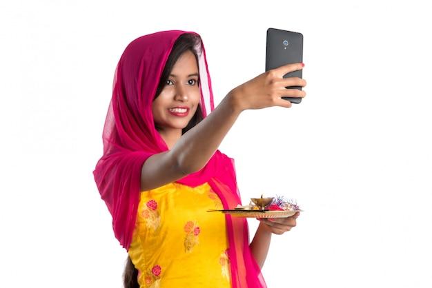 Piękna młoda szczęśliwa dziewczyna bierze selfie z pooja thali używać telefon komórkowego lub smartphone