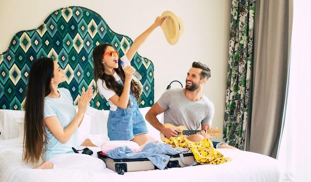Piękna młoda, szczęśliwa i podekscytowana rodzina w luksusowym pokoju hotelowym podczas rozpakowywania