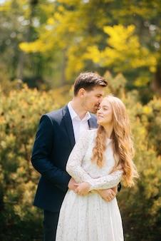 Piękna młoda szczęśliwa i właśnie para małżeńska obejmuje plenerowy w słonecznym dniu
