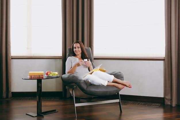 Piękna młoda szczęśliwa kobieta w domu siedzi na nowoczesnym krześle przed oknem, relaksując się w swoim salonie, czytając książkę i pijąc kawę lub herbatę