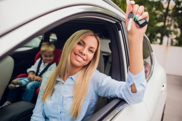 Piękna młoda szczęśliwa kobieta w nowym samochodzie z kluczami - outdoors