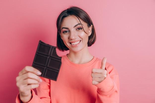 Piękna młoda szczęśliwa kobieta z czekolady na różowym tle i jasny makijaż