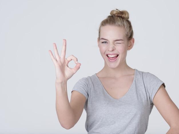 Piękna młoda szczęśliwa podekscytowana kobieta pokazuje dobrze znak na białym tle