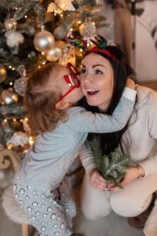 Piękna młoda szczęśliwa rodzina, mama i dziecko dziewczynka w modnej piżamie bawią się w pobliżu choinek i prezentów. ferie zimowe i nowy rok