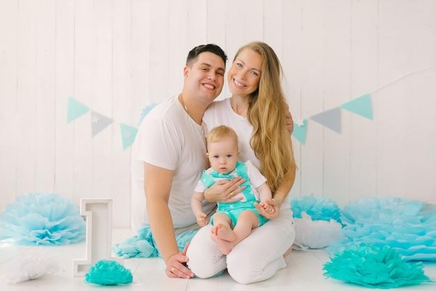 Piękna młoda szczęśliwa rodzina z rocznym dzieckiem ojciec przytula matkę dziecko ja