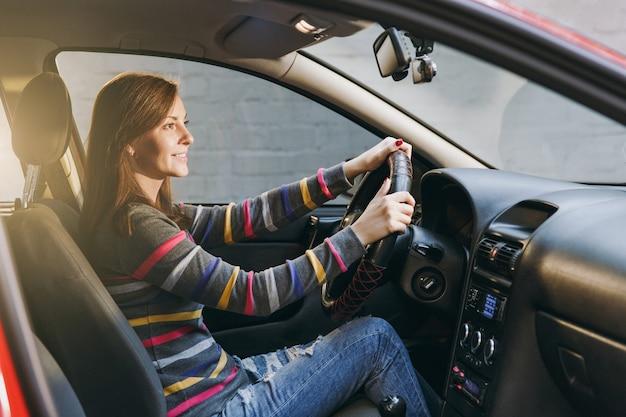 Piękna młoda szczęśliwa uśmiechnięta europejska brązowowłosa kobieta ze zdrową czystą skórą ubrana w pasiastą koszulkę siedzi w swoim czerwonym samochodzie z czarnym wnętrzem. koncepcja podróży i jazdy.