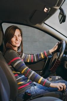 Piękna młoda szczęśliwa uśmiechnięta europejska brązowowłosa kobieta ze zdrową czystą skórą ubrana w pasiastą koszulkę siedzi w swoim samochodzie z czarnym wnętrzem. koncepcja podróży i jazdy.
