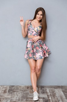Piękna młoda szczęśliwa uśmiechnięta pozytywna stylowa kobieta pokazująca znak pokoju i uśmiechnięta