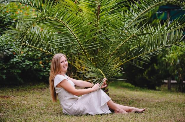 Piękna, młoda, szczupła, długowłosa blond dziewczyna w białej długiej sukni na tle palm i natury. indyk. model stylowy. moda. uśmiecha się szczęśliwy. ścieśniać