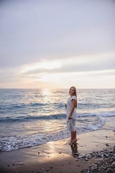 Piękna młoda szczupła dziewczyna jest na piaszczystej plaży nad morzem. w długiej białej sukni. fale. przeciw morzu indyk. wakacje. światło słoneczne. miejsce na tekst. noc. zachód słońca. horyzont.