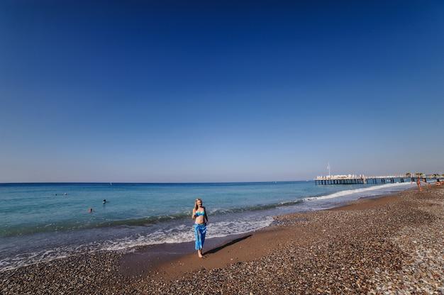 Piękna młoda szczupła dziewczyna stoi na piaszczystej plaży nad morzem. w niebieskim kostiumie kąpielowym, sukience, szalowej spódnicy sarongowej. indyk. wakacje. wakacje. światło słoneczne. miejsce na tekst