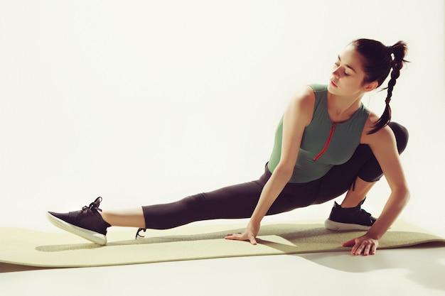 Piękna młoda szczupła kobieta robi ćwiczenia rozciągające na siłowni przed białym studio